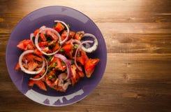 Tomates, cebolla, hinojo en una placa en un fondo de madera Foto de archivo