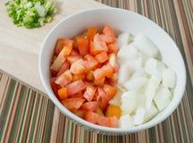 Tomates, cebollas y cebollas tajados de la primavera en tabla de cortar Foto de archivo libre de regalías