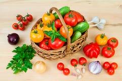 Tomates, cebollas y otras verduras en una cesta de mimbre en un wo Imagen de archivo libre de regalías