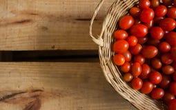 Tomates-cereja vermelhos pequenos dentro de cesta caixote de madeira em estilo rústico, foco seletivo. Tomato basket basket wood box lunch red meal red organic Stock Photos