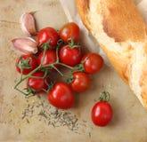 Tomates-cerises, ail, bruschette et herbes organiques sur un vieux hachoir en pierre rustique Image stock