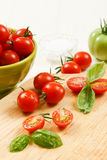 Tomates-cerises coupées en tranches avec le basilic Photos libres de droits