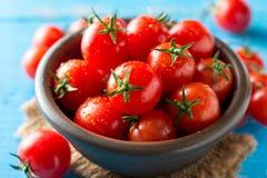 Tomates-cerises dans la cuvette en céramique sur le fond en bois rustique bleu Images libres de droits