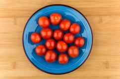 Tomates-cerises dans la glace bleue sur la table en bois Image stock