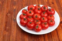 Tomates-cerises de la plaque blanche sur le fond en bois Photo stock