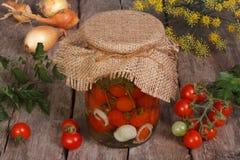 Tomates-cerises en boîte dans un pot en verre sur en bois Photos libres de droits