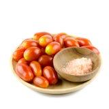 Tomates-cerises en bois de plat et sucre rose d'isolement sur le Ba blanc Photos stock