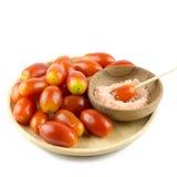 Tomates-cerises en bois de plat et sucre rose d'isolement sur le Ba blanc Photos libres de droits