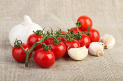 Tomates-cerises et ail au-dessus de tissu de jute photos stock