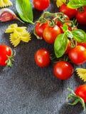Tomates-cerises et pâte organiques fraîches avec l'ail de basilic sur un fond foncé Images stock