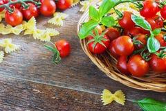 Tomates-cerises et pâte organiques fraîches avec l'ail de basilic sur un fond foncé Photos libres de droits