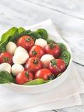 Tomates-cerises fraîches avec des feuilles de mozzarella et d'épinards Images stock