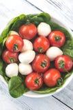 Tomates-cerises fraîches avec des feuilles de mozzarella et d'épinards Photographie stock