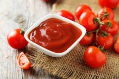Tomates-cerises fraîches avec le bol de ketchup sur un fond en bois gris Photo libre de droits