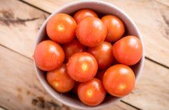 Tomates-cerises fraîches dans la cuvette sur le fond en bois Image stock