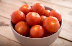 Tomates-cerises fraîches dans la cuvette sur le fond en bois Photographie stock libre de droits