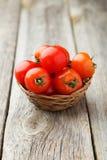 Tomates-cerises fraîches dans le panier sur un fond en bois gris Photos stock