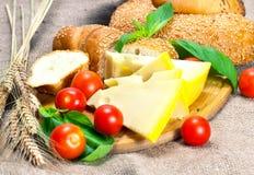 Tomates-cerises fromage et pain de céréale sur la planche à découper Photographie stock libre de droits