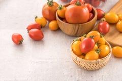 Tomates-cerises jaunes et rouges fraîches dans un panier sur un panneau de ciment, fin, l'espace de copie, vue supérieure photographie stock