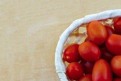 Tomates-cerises mûres dans un panier blanc sur les légumes juteux d'une récolte en bois d'automne de l'espace de copie de fond photos libres de droits