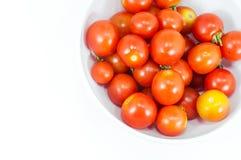 Tomates-cerises mûres dans une cuvette sur le blanc Photos libres de droits