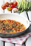 Tomates-cerises rôties dans la casserole de sauce Légumes rôtis sur le fond rustique blanc Photo stock