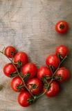 Tomates-cerises red delicious fraîches sur un vieux dessus de table en bois b Image stock
