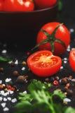 Tomates-cerises rouges juteuses sur un fond noir avec les épices, le sel brut et les verts Tomates douces et mûres coupées en tra image stock