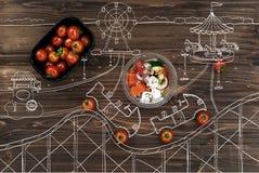 Tomates-cerises rouges se trouvant près de la cuvette avec de la salade grecque Images libres de droits
