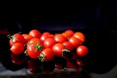Tomates-cerises rouges sur le contexte noir brillant Photos libres de droits