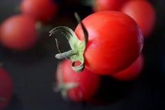 Tomates-cerises rouges sur le verre avec le trouble Photo stock