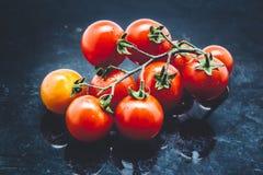 Tomates-cerises sur le fond foncé en métal Image stock