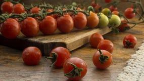 Tomates-cerises sur le hachoir et la table en bois Images stock