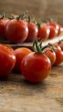 Tomates-cerises sur le hachoir et la table en bois Images libres de droits