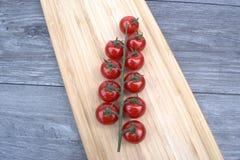 Tomates-cerises sur un panneau de découpage Photo stock