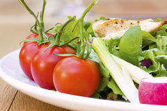 Tomates-cerises sur une fin de plaque de salade vers le haut Images stock