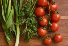 Tomates-cerises, tas d'aneth, oignon vert et ramsons Photos libres de droits