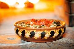 Tomates cocidos con las setas en un cuenco de la arcilla con un ornamento en el fondo de una estufa madera-ardiendo imagenes de archivo