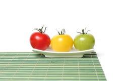 Tomates colorées sur le couvre-tapis en bambou Photos libres de droits