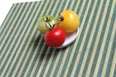 Tomates colorées sur le couvre-tapis en bambou Photo libre de droits