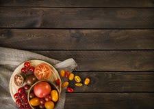 Tomates coloridos em uma tabela de madeira Fotografia de Stock