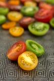 Tomates coloridos en una placa Fotos de archivo libres de regalías
