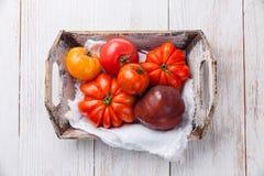 Tomates coloridos frescos maduros en caja de madera Fotografía de archivo libre de regalías