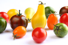 Tomates coloridos na tela branca Fotografia de Stock