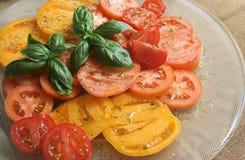 Tomates com manjericão e pingamento Fotografia de Stock Royalty Free