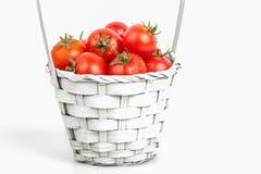 Tomates con las hojas verdes aisladas en el fondo blanco maduro a Imagen de archivo