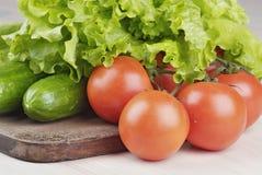 Tomates, concombres et salade sur le panneau de découpage Photographie stock