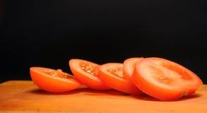 Tomates cortados em uma tabuleta de madeira Imagens de Stock Royalty Free