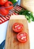 Tomates cortados maduros em uma placa de madeira Fotos de Stock