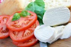 Tomates cortados, pão e queijo fresco do Mozzarella Imagens de Stock